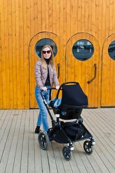 Młoda matka chodzi z dzieckiem w wózku na tle drzwi przemysłowych z iluminatorami.
