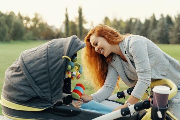 Młoda matka, ciesząc się spacer w parku z dzieckiem