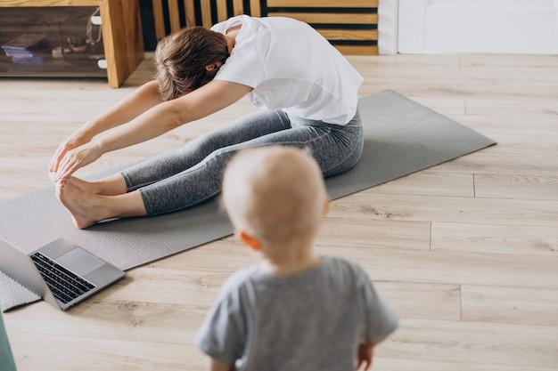 Młoda matka ćwiczy jogę z małym synem na macie