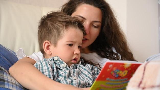 Młoda matka czyta dziecku książkę przed snem.