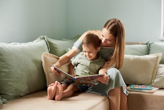 Młoda matka, czyta książkę swojemu dziecku, chłopakowi w salonie ich domu, promienie słońca wpadają przez okno