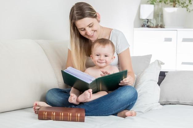 Młoda matka czyta książkę swojemu uśmiechniętemu chłopcu