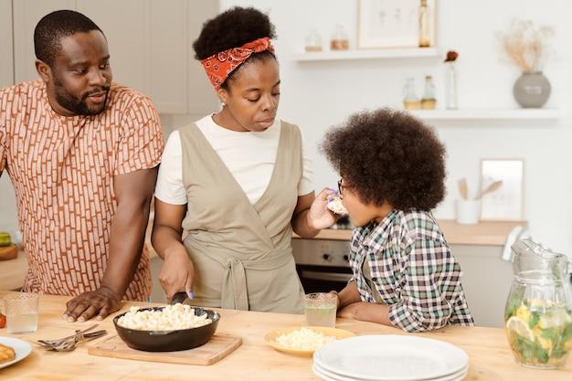 Młoda matka daje swojemu uroczemu synkowi trochę makaronu do smaku
