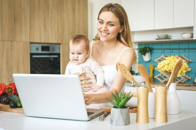 Młoda matka gotuje i bawi się z córką w nowoczesnej kuchni. patrząc na laptopa z uśmiechem.