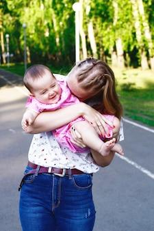 Młoda matka gra i śmiejąc się dziecko w zielonym parku.