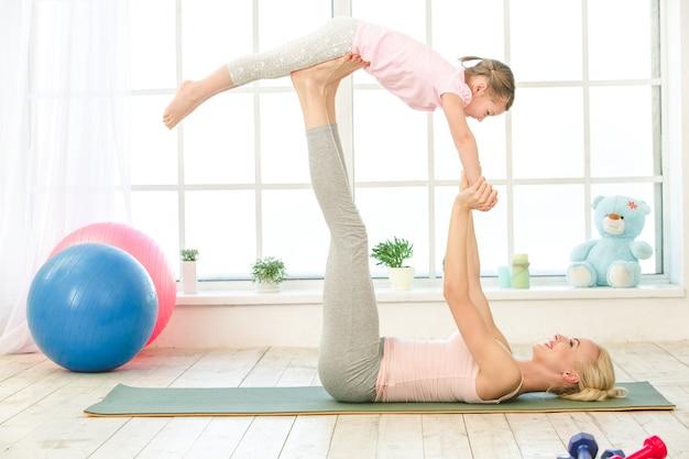 Młoda matka i córka ćwiczą razem w pomieszczeniu
