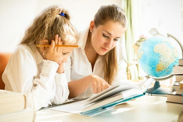 Młoda matka i córka czytają podręcznik podczas odrabiania lekcji