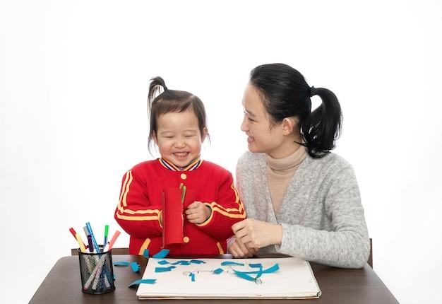 Młoda matka i córka gra cięcia papieru