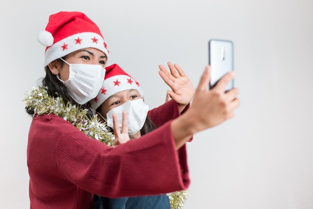 Młoda matka i córka mają na sobie maskę i świąteczny kapelusz, rozmawiając przez smartfona. świętowanie bożego narodzenia z dystansem.