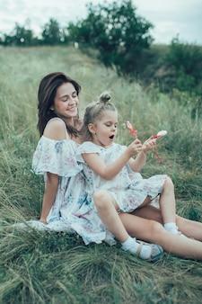 Młoda matka i córka na zielonej trawie