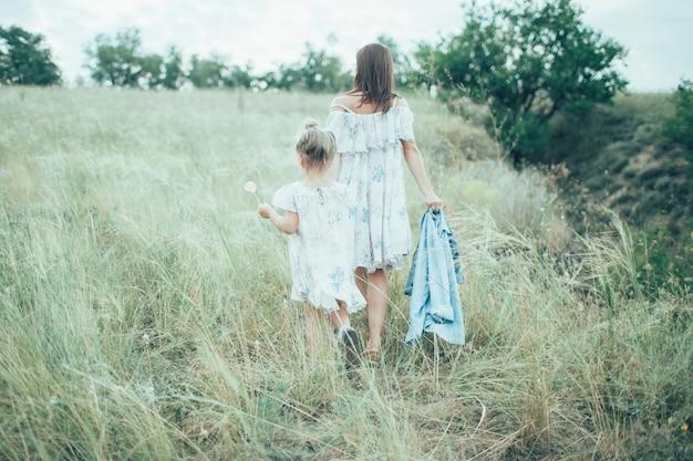 Młoda matka i córka na zielonej trawy tle
