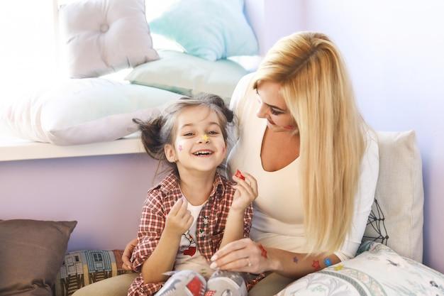 Młoda matka i córka nakładają naklejki na twarz