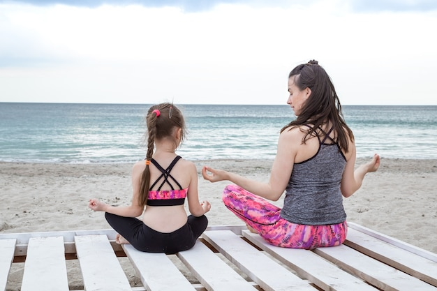 Młoda matka i córka praktykują jogę i medytację na plaży.