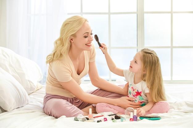 Młoda matka i córka rano na łóżku w pomieszczeniu