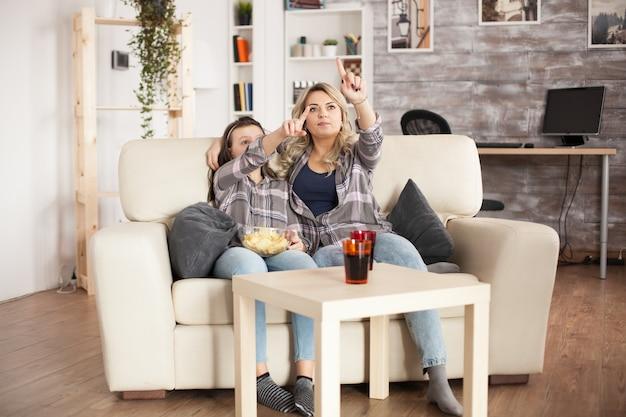 Młoda matka i córka siedzi na kanapie za pomocą rozszerzonej rzeczywistości, aby zmienić kanał telewizyjny.