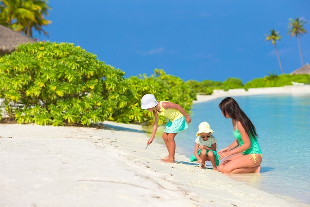 Młoda matka i dwie jej małe dziewczynki na egzotycznej plaży w słoneczny dzień
