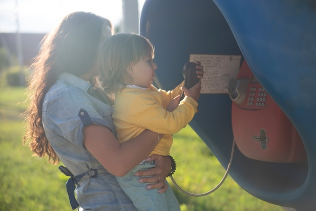 Młoda matka i dziecko dzwonią na telefon stacjonarny ulicy w budce telefonicznej we wsi w lecie. spacery z rodzinnym letnim słonecznym dniem w promieniach słońca. artystyczne skupienie