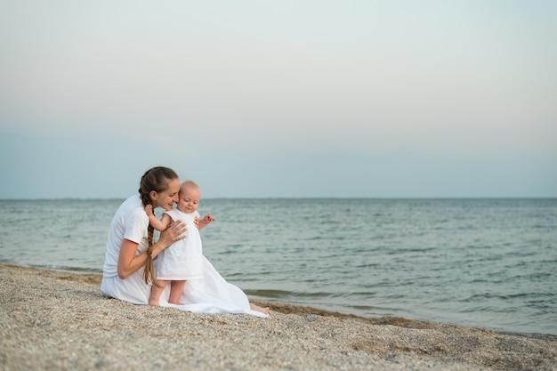 Młoda matka i dziecko siedzi na piaszczystej plaży. wakacje nad morzem z małymi dziećmi