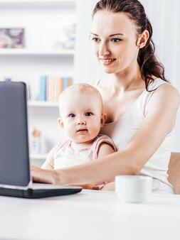 Młoda matka i dziecko używają laptopa do komunikacji z babcią v