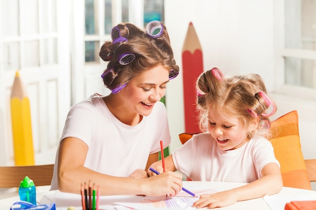 Młoda matka i jej córeczka rysują ołówkami w domu