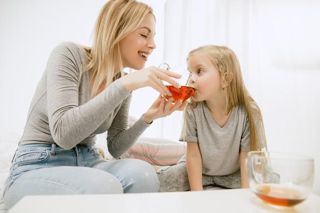 Młoda matka i jej córeczka w domu w słoneczny poranek. miękkie pastelowe kolory. szczęśliwego rodzinnego weekendu. koncepcja dnia matki. koncepcje rodziny, miłości, stylu życia, macierzyństwa i chwil czułych.