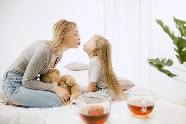 Młoda matka i jej córeczka w domu w słoneczny poranek. miękkie pastelowe kolory. szczęśliwego rodzinnego weekendu.