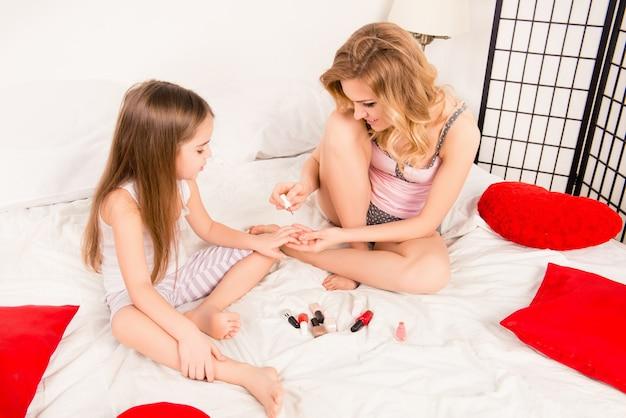 Młoda matka i jej córka dziecko dziewczynka malowanie paznokci