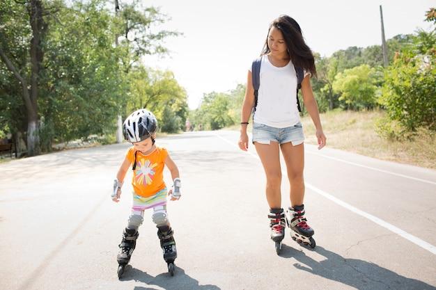 Młoda matka i jej córka jeżdżą na rolkach na drodze samotnie. baw się dobrze razem. matka uczy córkę jazdy na łyżwach. czas letni