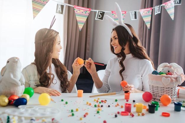 Młoda matka i jej córka przygotowują się do wielkanocy. łamią się jajka i uśmiechają. młoda kobieta i jej córka noszą uszy królika. dekoracja i malowanie na stole.
