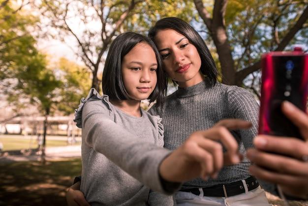 Młoda matka i jej córka robią zdjęcie telefonem w parku w słoneczny dzień.