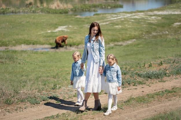 Młoda matka i jej córki bliźniaczki idą ścieżką we wsi.