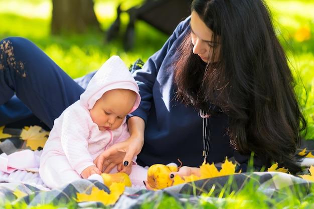 Młoda matka i jej dziecko bawiące się w jesiennym parku leżąc razem na dywanie na trawie z żółtymi liśćmi i dojrzałym złotym jabłkiem