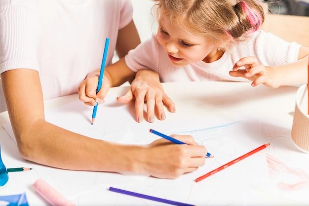 Młoda matka i jej mała córka rysują ołówkami w domu