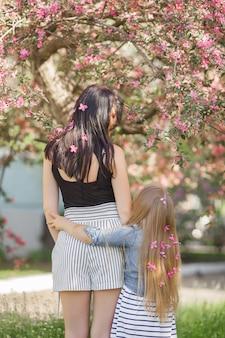 Młoda matka i jej mała dziewczynka z kwiatami we włosach