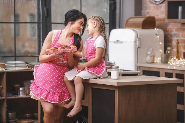 Młoda matka i jej mała śliczna córka ma zabawę w kuchni