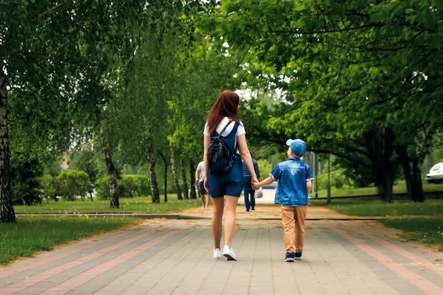 Młoda matka i jej syn idą wzdłuż pięknego letniego parku.