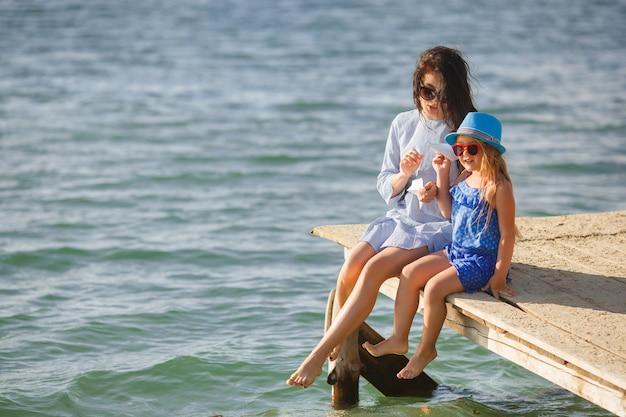 Młoda matka i jej urocza córka nad morzem odpalają papierowe samoloty w powietrzu i śmieją się