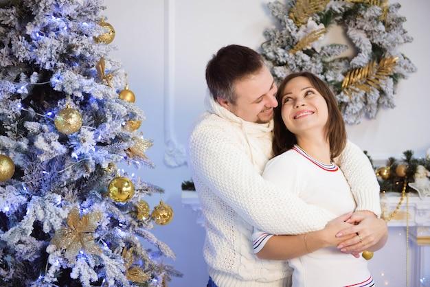 Młoda matka i ojciec świętuje boże narodzenie w domu.