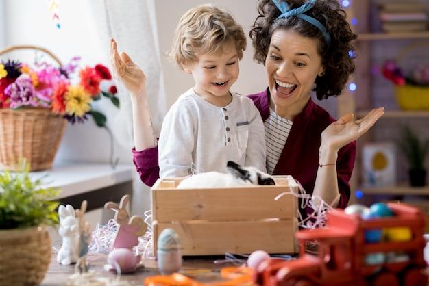 Młoda matka i syn bawi się z króliczkiem