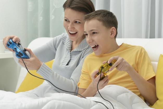 Młoda matka i syn grają w grę komputerową w łóżku