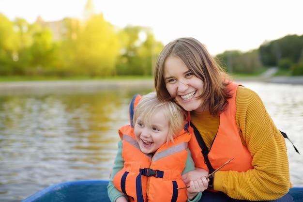 Młoda matka i synek na łodzi na rzece lub stawie w słoneczny letni dzień.
