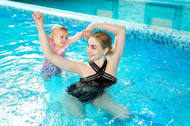 Młoda matka, instruktor pływania i szczęśliwa mała dziewczynka w basenie. uczy pływać niemowlę.