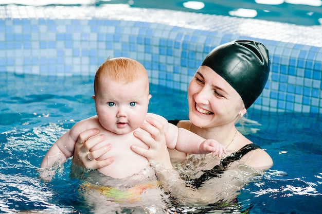 Młoda matka, instruktor pływania i szczęśliwa mała dziewczynka w brodziku. uczy niemowlę pływać. ciesz się pierwszym dniem kąpieli w wodzie. mama trzyma rękę dziecko przygotowuje się do nurkowania. robienie ćwiczeń