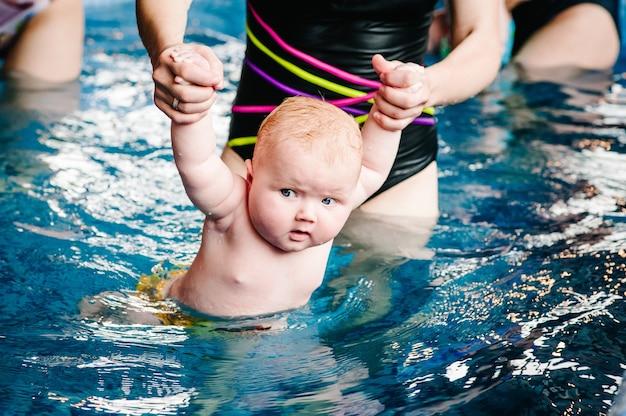 Młoda matka, instruktor pływania i szczęśliwa mała dziewczynka w brodziku. uczy niemowlę pływać.