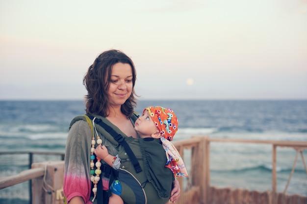 Młoda matka jest na plaży z dzieckiem na temblaku