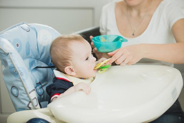 Młoda matka karmi swojego chłopca łyżką
