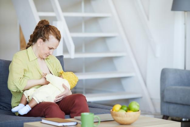 Młoda matka karmi swojego noworodka na rękach, siedząc na kanapie w salonie