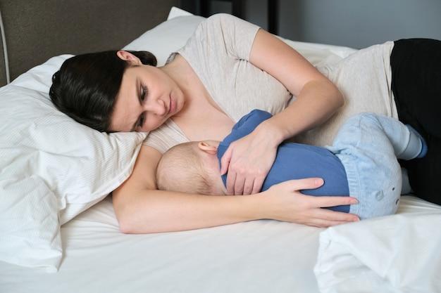 Młoda matka karmiąca piersią swojego syna, mama karmiąca przytulająca dziecko, matka i maluch leżą razem w domu na łóżku, dziecko je i zasypia