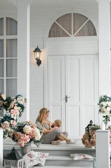 Młoda matka karmienie piersią dziecka, siedząc na podłodze w pobliżu domu ganek na zewnątrz.