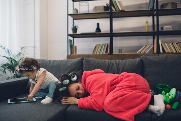 Młoda matka ma depresję poporodową. smutna i zmęczona kobieta z ppd. nie chce się bawić z córką